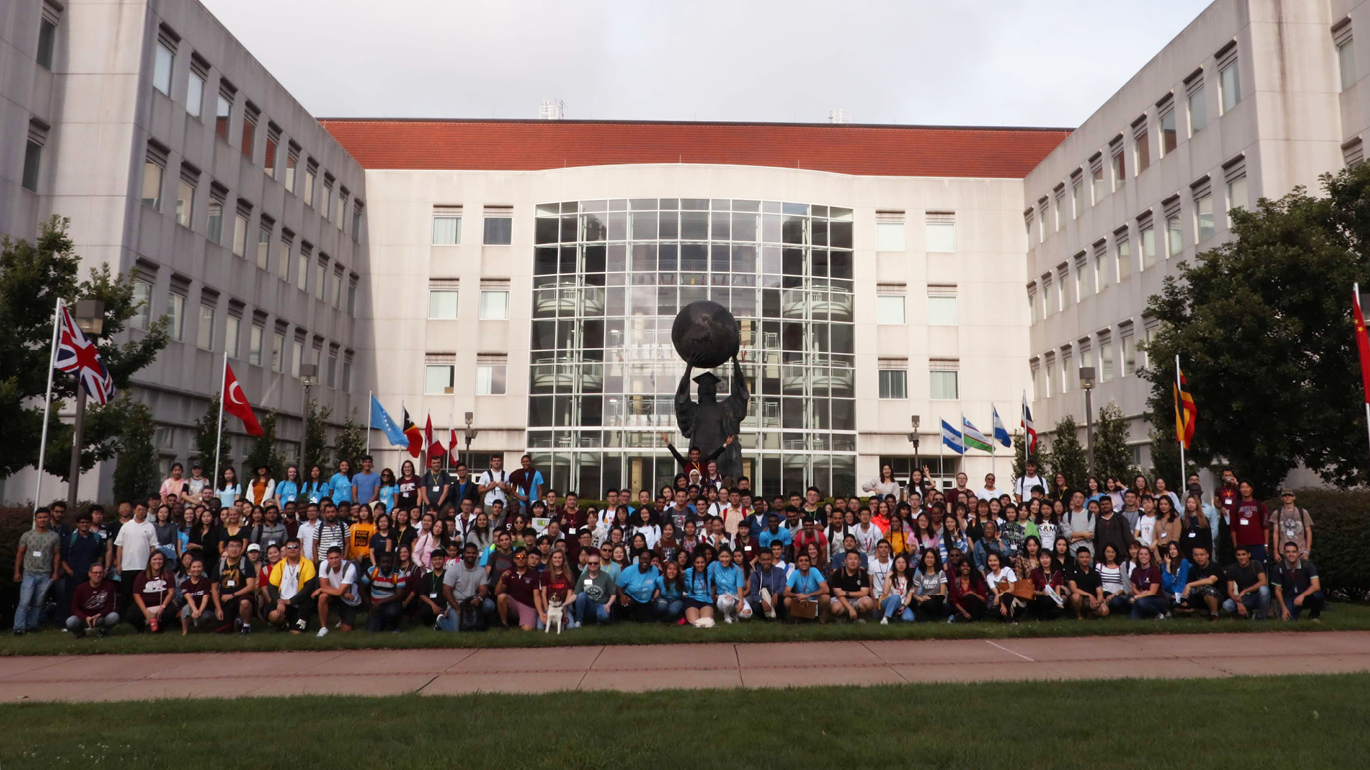 Over 200 new international students pose with the Citizen Scholar statue on campus at Missouri State during orientation.